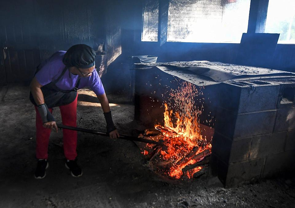 Helen Turner, owner of Helen's BBQ in Brownsville, Tennessee, kindles a fire inside the smokehouse in the back of her restaurant. The fire is started on one side of the smokehouse and is transferred to the smoker where the meats are prepared.