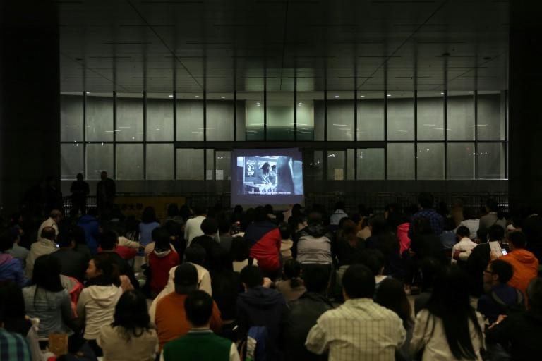 Members of the public watch the dystopian Hong Kong independent film 'Ten Years' on a make-shift screen in the Chinese city