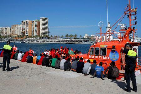 FILE PHOTO: Migrants rest after arriving on a rescue boat at the port of Malaga
