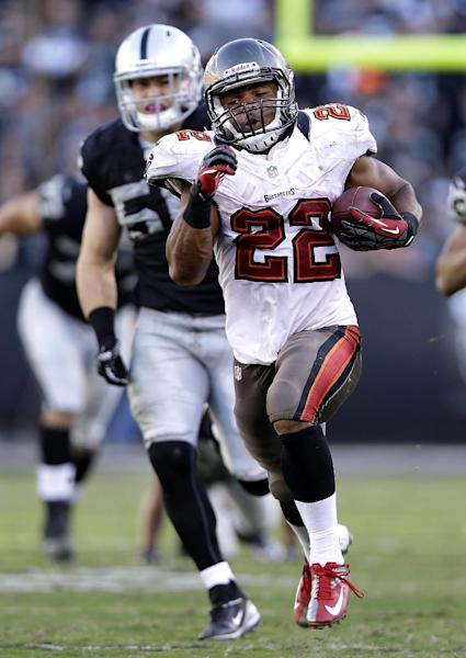 Tampa Bay Buccaneers running back Doug Martin (22) runs past Oakland Raiders linebacker Miles Burris (56) to score on a 67-yard touchdown during the third quarter of an NFL football game in Oakland, Calif., Sunday, Nov. 4, 2012. (AP Photo/Marcio Jose Sanchez)