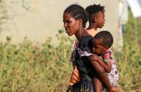 Ethiopian woman who fled war in Tigray region, carries a child at the Fashaga camp on the Sudan-Ethiopia border in Al-Qadarif state