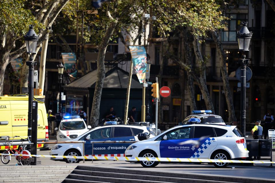 <p>Policemen stand next to vehicles in a cordoned off area after a van ploughed into the crowd, injuring several persons on the Rambla in Barcelona on August 17, 2017. (Josep Lago/AFP/Getty Images) </p>