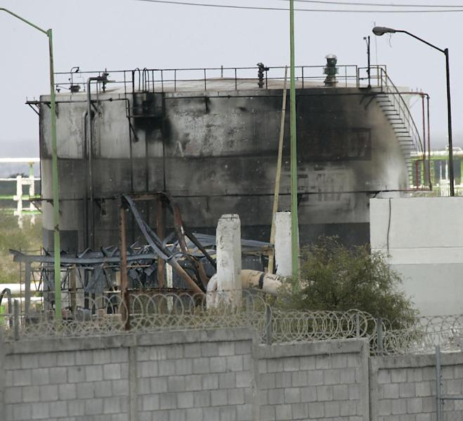 Severely burnt out Pemex gas tanks at the Petroleos Mexicans pipeline distribution center on the outskirts of Reynosa, Mexico, reveals some of the extent of the damage caused by the gas explosion, Wednesday Sept. 19, 2012. The death toll in a pipeline fire at a distribution plant near the U.S. border has risen to 29, Mexico's state-owned oil company said Wednesday. At least 46 others were injured, and more might be missing. (AP Photo/The Monitor, Delcia Lopez)