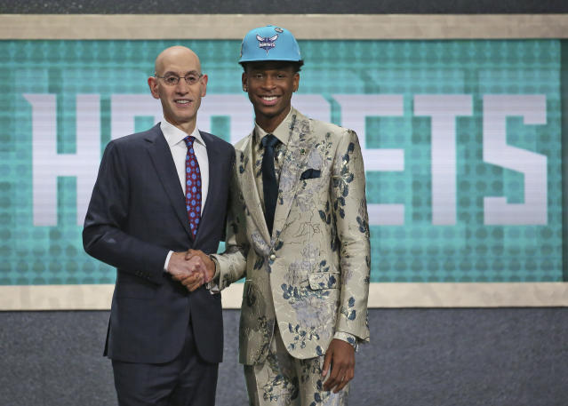 Shai Gilgeous-Alexander, right, poses in an eccentric suit he designed with NBA Commissioner Adam Silver before getting traded to the Clippers. (AP Photo).