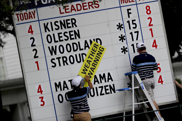 A course worker puts up a weather warning sign as play was suspended during the second round of the PGA Championship golf tournament at the Quail Hollow Club Friday, Aug. 11, 2017, in Charlotte, N.C. (AP Photo/John Bazemore)