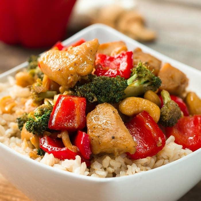 Bowl of chicken and veggies in sauce over rice