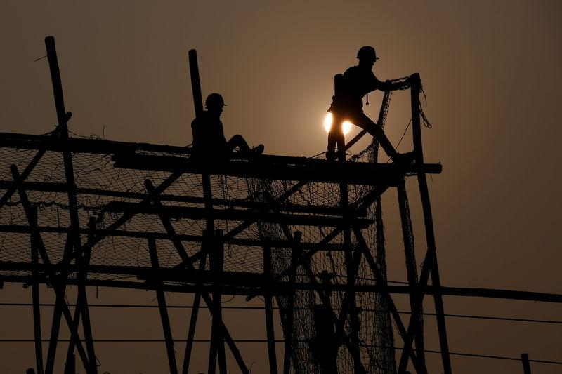 Workers build a wooden scaffolding at a construction site in Beijing