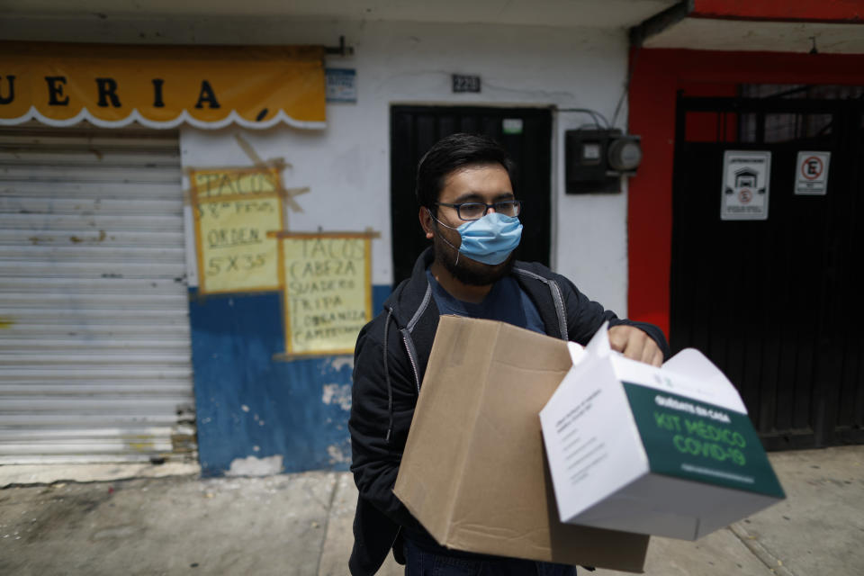 Armando Beltran, 25, whose mother is quarantined in their home with COVID-19 symptoms including fever, headache, exhaustion, and a loss of the sense of smell, carries medical and food supply kits dropped off by city government workers, in the Coyoacan district of Mexico City, Thursday, April 9, 2020. To help halt the spread of the new coronavirus, the Mexican megalopolis is making home deliveries to households with a symptomatic person, providing kits containing food staples, face masks, gloves, antibacterial gel, paracetamol, a thermometer, and benefits cards with a balance of 1000 pesos (around $42). (AP Photo/Rebecca Blackwell)