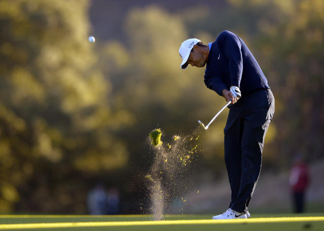 Tiger Woods makes his approach shot on the 18th hole during the first round of the Northwestern Mutual World Challenge golf tournament at Sherwood Country Club, Thursday, Dec. 5, 2013, in Thousand Oaks, Calif. (AP Photo/Mark J. Terrill)