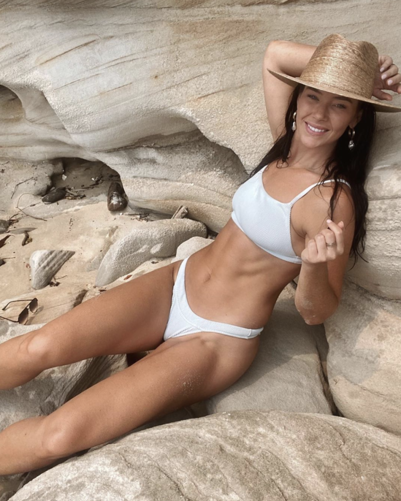 Bachelor In Paradise season three cast member Brittany Hockley wearing a white bikini and straw hat while reclining on a rock