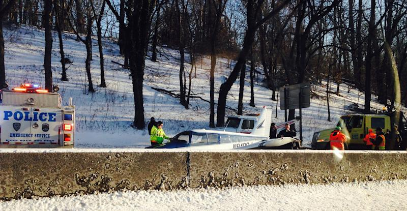 In this photo provided by Patricia Sapol, emergency personnel respond to a light airplane that made an emergency landing on the Major Deegan Expressway in the Bronx borough of New York, Saturday, Jan. 4, 2014. No major injuries were reported but northbound traffic was halted as fuel was removed from the aircraft before it could be removed from the highway. (AP Photo/Patricia Sapol)