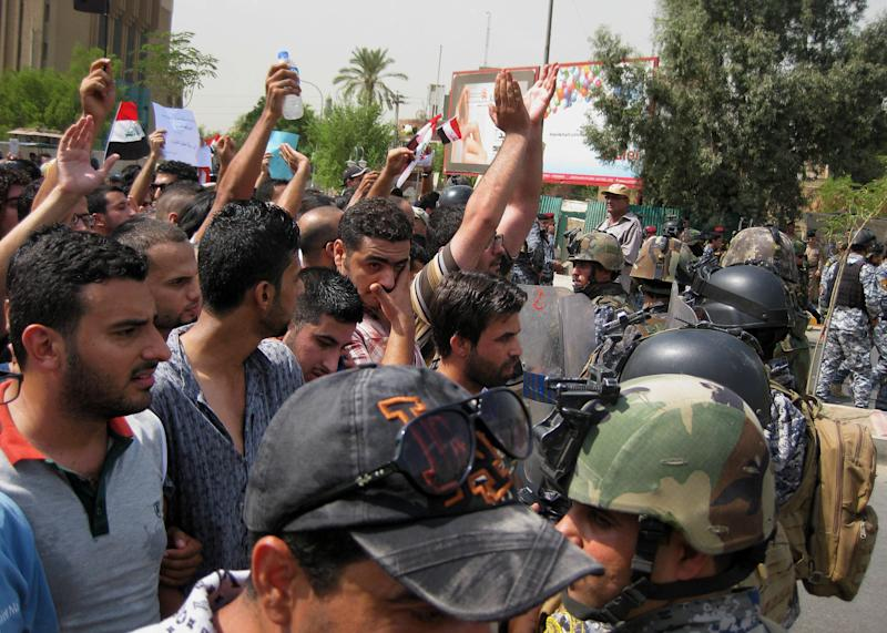 Protesters chant slogans against the Iraqi parliament in Baghdad, Iraq, Saturday, Aug. 31, 2013. Protesters held rallies in Baghdad and the southern Iraqi city of Basra to demand to cancel parliamentarians' pensions. (AP Photo/ Hadi Mizban)