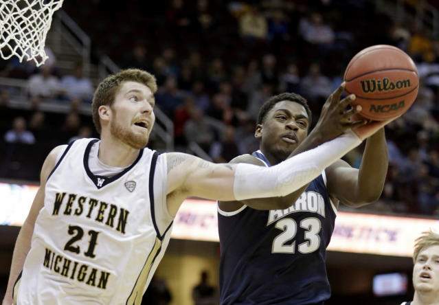 Western Michigan's Shayne Whittington (21) and Akron's Isaiah Johnson (23) battle for a rebound during the first half of an NCAA college basketball game at the Mid-American Conference tournament Friday, March 14, 2014, in Cleveland. (AP Photo/Tony Dejak)