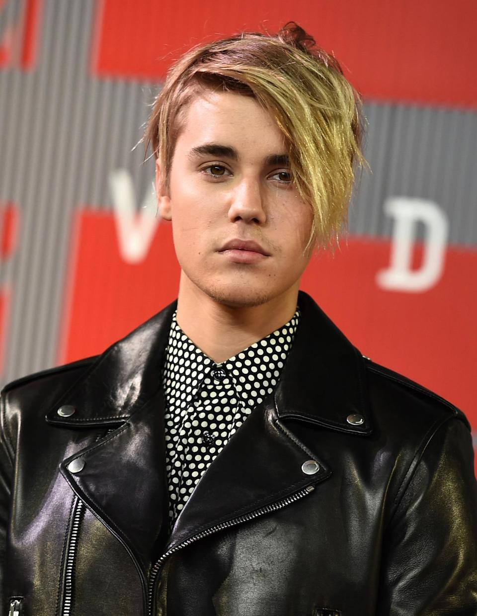 """<p>Ever since Biebs burst on the scene with his bowl cut, the pop singer has been all about his hair. He debuted a new look at the VMAs: Piecey, messy, and blonde with one side shorter than the other. It earned him a shoutout from the stage from host Miley Cyrus who noted, """"I like your swoop!""""</p><p>Source: Getty Images</p>"""