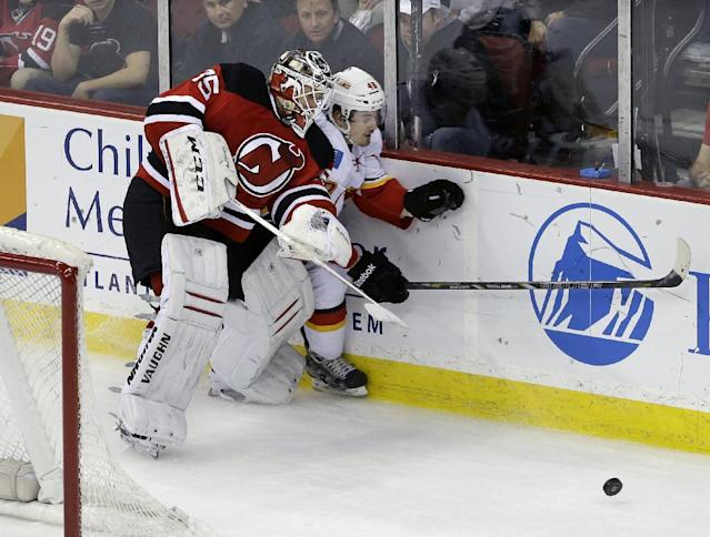 New Jersey Devils goalie Cory Schneider (35) checks Calgary Flames' Bryce Van Brabant (48) into the boards during the second period of an NHL hockey game in Newark, N.J., Monday, April 7, 2014. (AP Photo/Mel Evans)