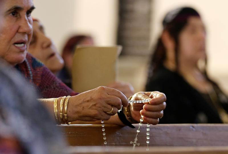 Iraqi Christians fleeing the violence in the towns of Qaraqush and Bartala pray at the Saint George church on July 1, 2014 in Arbil