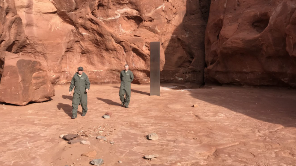A strange monolith stands in the middle of the Utah desert, as two government employees walk near it.