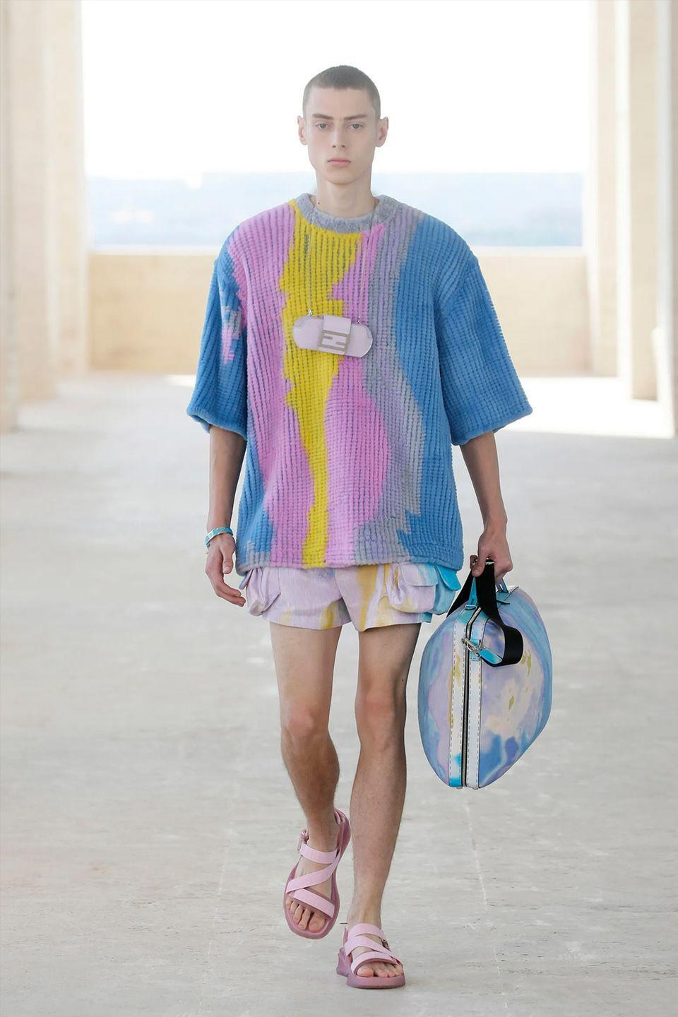"""<p><a href=""""https://www.esquire.com/uk/style/a35249880/fendi-men-fw-21/"""" rel=""""nofollow noopener"""" target=""""_blank"""" data-ylk=""""slk:If last season's Fendi show was the pyjama party"""" class=""""link rapid-noclick-resp"""">If last season's Fendi show was the pyjama party</a>, the most recent outing was the actual party. But rather than tune into a familiar strain of 2am dark lit, smoking indoors party (y'know the sort: sexy, rippling shirts, hard won summer bods etc), creative director Silvia Venturini Fendi played on the concept of newfound freedoms in figurative and literal ways.</p><p>So that meant motifs inspired by Rome, and TikTok adjacent crop tops, and cargo shorts that fell pruriently short of the golden five inch inseam. It's not the stuff of a cramped, sweaty Hackney Wick club. This is the carefree, permasmiling day party – and they're always so much better anyway. </p><p><strong>MC</strong></p>"""