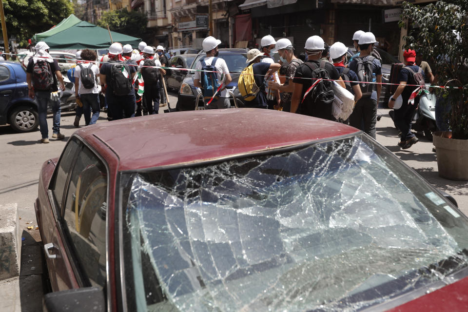 Lebanese youth who volunteered to help clean damaged homes and give other assistance, pass in front of a car that was damaged by last week's explosion, in Beirut, Lebanon, Tuesday, Aug. 11, 2020. The explosion that tore through Beirut left around a quarter of a million people with homes unfit to live in. But there are no collective shelters, or people sleeping in public parks. That's because in the absence of the state, residents of Beirut opened their homes to relatives, friends and neighbors. (AP Photo/Hussein Malla)