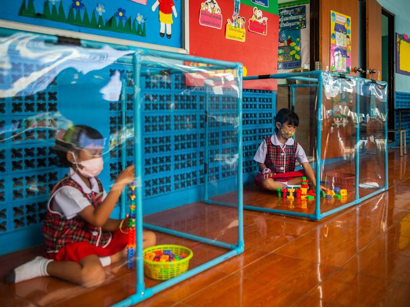 Two Thai pupils play behind plastic screens in separate play areas at the Wat Khlong Toey School on August 10, 2020 in Bangkok, Thailand: Lauren DeCicca/Getty Images