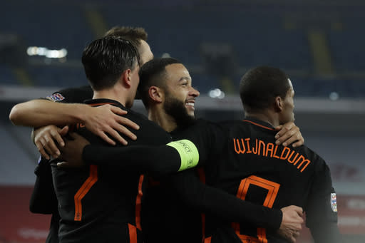 Netherlands' Steven Berghuis, left, and Memphis Depay, laughing, celebrate with Georginio Wijnaldum, right, who scored his side's second goal during the Nations League soccer match between Poland and The Netherlands at Silesian Stadium in Chorzow, Poland, Wednesday, Nov. 18, 2020. (AP Photo/Czarek Sokolowski)