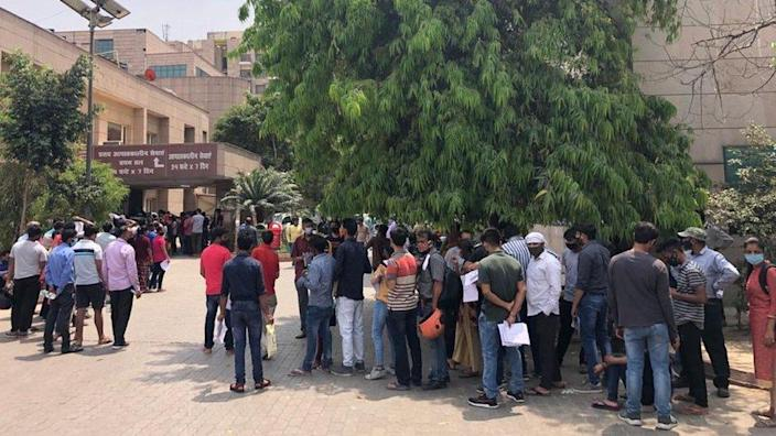 People waiting to be screened and tested outside a government-run hospital in Noida.