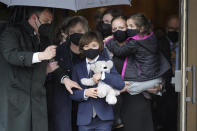 """Logan Evans, 9, center, son of the late U.S. Capitol Police officer William """"Billy"""" Evans, holds a stuffed toy as he departs St. Stanislaus Kostka Church with his grandmother Janice Evans, behind center left, and his mother Shannon Terranova, center right, who holds his sister Abigail Evans, 7, right, following a funeral Mass for his father, in Adams, Mass., Thursday, April 15, 2021. Evans, a member of the U.S. Capitol Police, was killed on Friday, April 2, when a driver slammed his car into a checkpoint he was guarding at the Capitol. (AP Photo/Steven Senne)"""