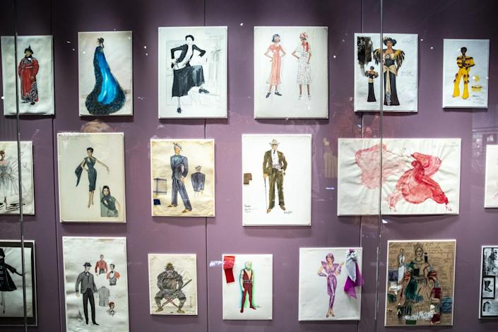 Costume design sketches hang on the wall