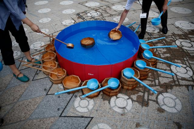<p>People fill wooden buckets with water during a water sprinkling event called Uchimizu which is meant to cool down the area, in Tokyo on July 23, 2018. (Photo: Martin Bureau/AFP/Getty Images) </p>