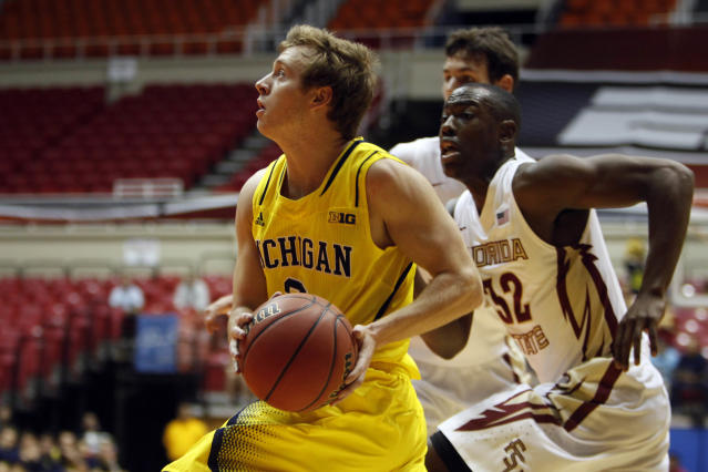 Michigan guard Spike Albretch, left, drives to the basket followed by Florida State guard Montay Brandon during an NCAA college basketball game in San Juan, Puerto Rico, Friday, Nov. 22, 2013. (AP Photo/Ricardo Arduengo)