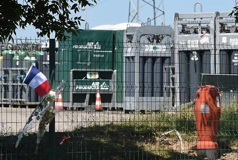 A French flag and flowers are placed on the fence of the Air Products gas factory where the head of the decapitated man was found in a suspected Islamist attack two days earlier in Saint-Quentin-Fallavier near Lyon on June 28, 2015 (AFP Photo/Philippe Desmazes)