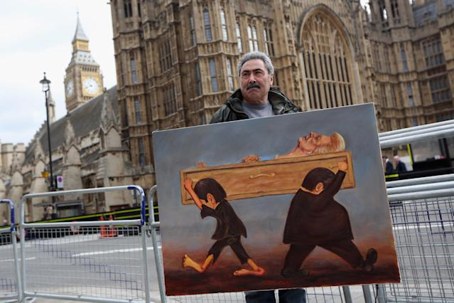 LONDON, ENGLAND - APRIL 15: Artist Kaya Mar stands with his latest painting depicting the funeral of Baroness Thatcher entitled 'A Nation Divided' outside the Houses of Parliament on April 15, 2013 in London, England. Lady Thatcher's coffin will be carried on a gun carriage though the City of London to St Paul's cathedral where a funeral service will be held on April 17, 2013. (Photo by Oli Scarff/Getty Images)
