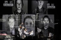 """Portraits of Auschwitz death camp prisoners are displayed on a mesh as actresses of the Jewish State Theatre, perform during the premiere of the """"The Beautiful Days of My Youth"""" play, based on the diary of Romanian Jewish Holocaust survivor Ana Novac, in Bucharest, Friday, Oct. 16, 2020. Maia Morgenstern, head of the Jewish State Theater and a Romanian Jewish actress best known for playing Mary in Mel Gibson's controversial 2004 movie """"The Passion of the Christ,"""" described the play's staging in an interview with The Associated Press as an """"all-feminine project."""" (AP Photo/Andreea Alexandru)"""