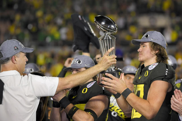 Oregon quarterback Justin Herbert and head coach Mario Cristobal celebrate after being Wisconsin in the Rose Bowl. (AP Photo/Mark J. Terrill)