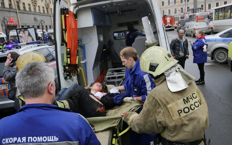 An injured person is helped by emergency services outside Sennaya Ploshchad metro station - Credit: Anton Vaganov/Reuters