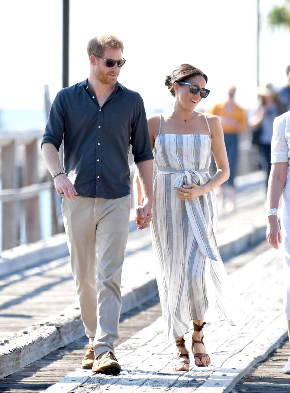 Prince Harry and Meghan take a stroll down the Kingfisher Bay jetty. Photo: Getty