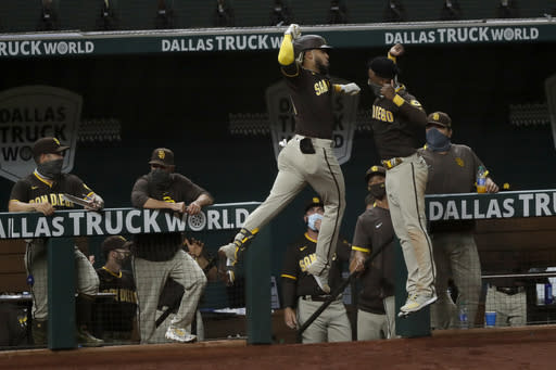 San Diego Padres' Fernando Tatis Jr., center left, and Jurickson Profar, center right, leap and celebrate in front of the dugout after Tatis Jr., hit a three-run home run in the seventh inning of a baseball game against the Texas Rangers in Arlington, Texas, Monday Aug. 17, 2020. (AP Photo/Tony Gutierrez)