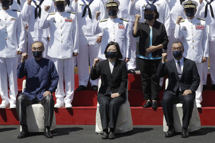 Taiwan's President Tsai Ing-wen, center, cheers with officers during the commissioning ceremony of the the domestically made Ta Jiang warship at the Suao naval base in Yilan county, Taiwan, Thursday, Sept. 9, 2021. Taiwan's president oversaw the commissioning of the new domestically made navy warship Thursday as part of the island's plan to boost indigenous defense capacity amid heightened tensions with China. (AP Photo/Chiang Ying-ying)