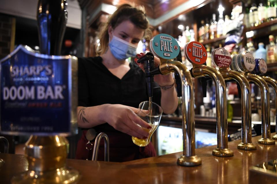 A server wearing a face mask or covering due to the COVID-19 pandemic, pours a pint of Camden Pale Ale inside a pub in Mayfair, London.