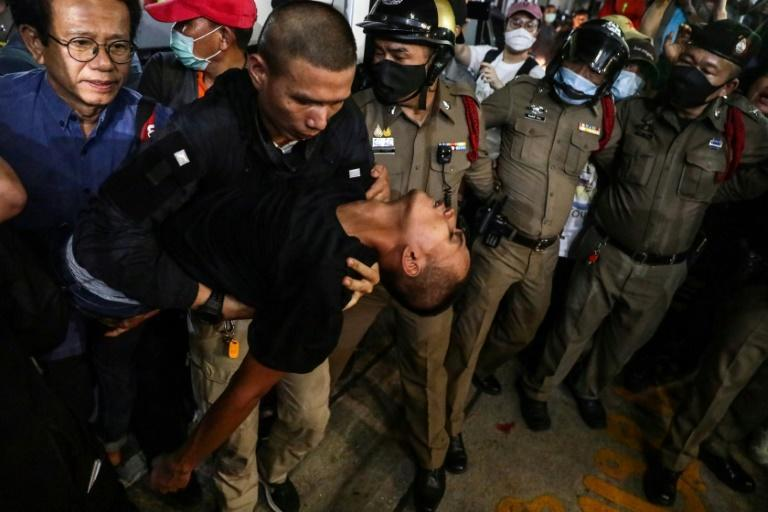 "Thai pro-democracy activist Panupong ""Mike"" Jadnok is carried to an ambulance outside a Bangkok police station"