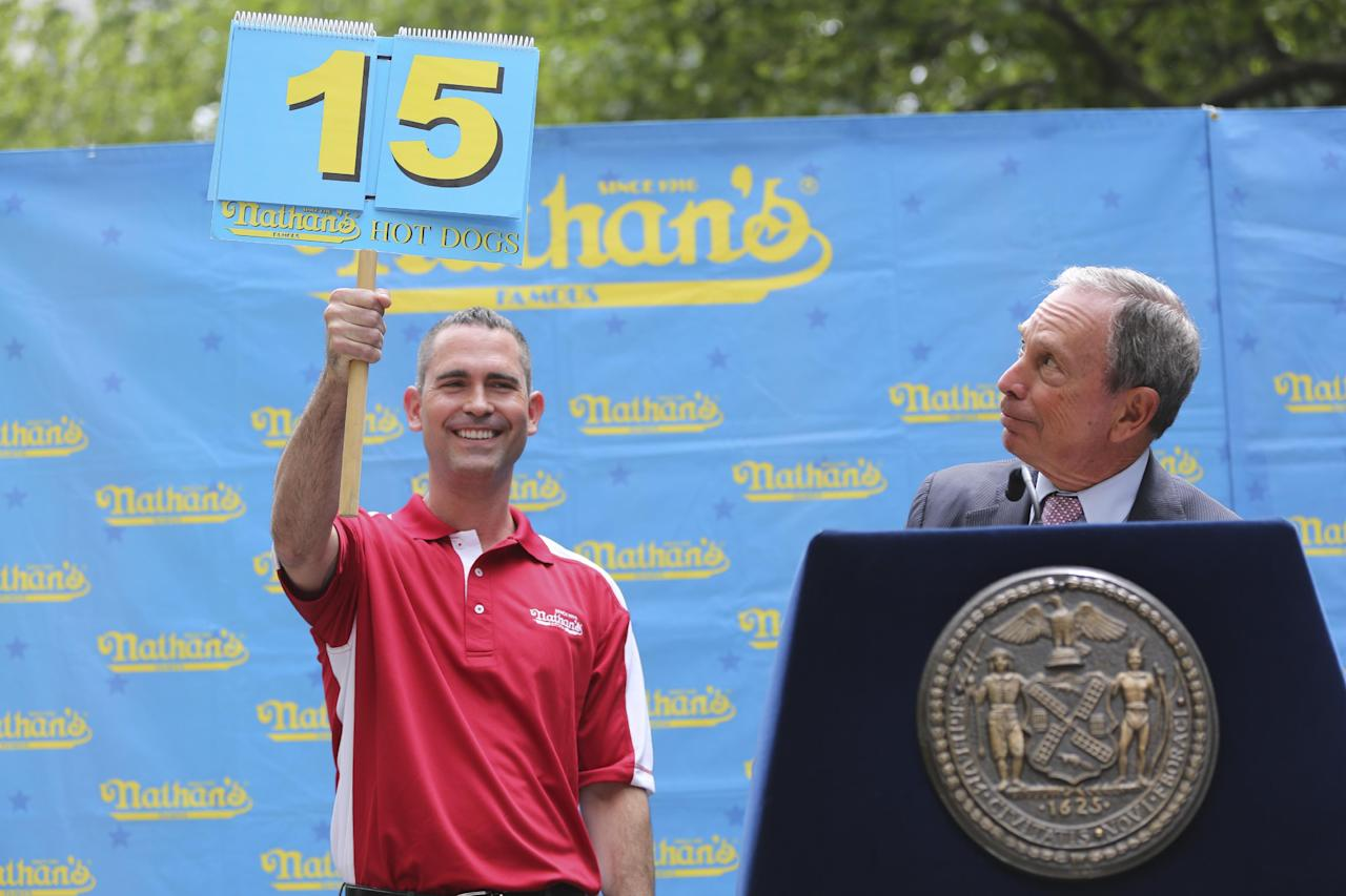 New York City Mayor Michael Bloomberg looks to see how many puns he made while making a speech during the official weigh-in for the Nathan's Fourth of July hot dog eating contest, Wednesday, July 3, 2013 at City Hall park in New York. (AP Photo/Mary Altaffer)