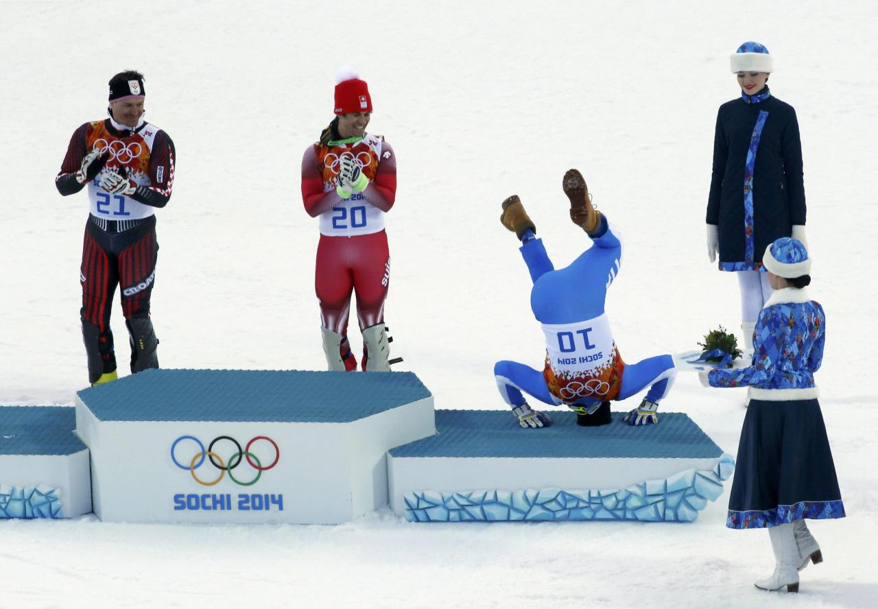 Third-placed Italy's Christof Innerhofer (2nd R) does a somersault on the podium as winner Switzerland's Sandro Viletta (2nd L) and second-placed Croatia's Ivica Kostelic (L) laugh after the men's alpine skiing super combined event at the Sochi 2014 Winter Olympics at the Rosa Khutor Alpine Center February 14, 2014. REUTERS/Stefano Rellandini (RUSSIA - Tags: SPORT SKIING OLYMPICS TPX IMAGES OF THE DAY)