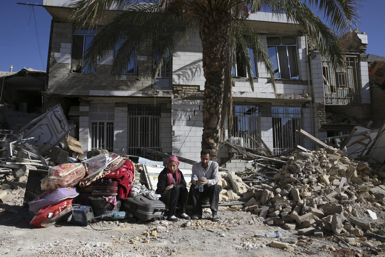<p>Survivors sit in front of a destroyed house on the earthquake site in Sarpol-e-Zahab in western Iran, Nov. 14, 2017. Rescuers are digging through the debris of buildings felled by the Sunday earthquake in the border region of Iran and Iraq. (Photo: Vahid Salemi/AP) </p>