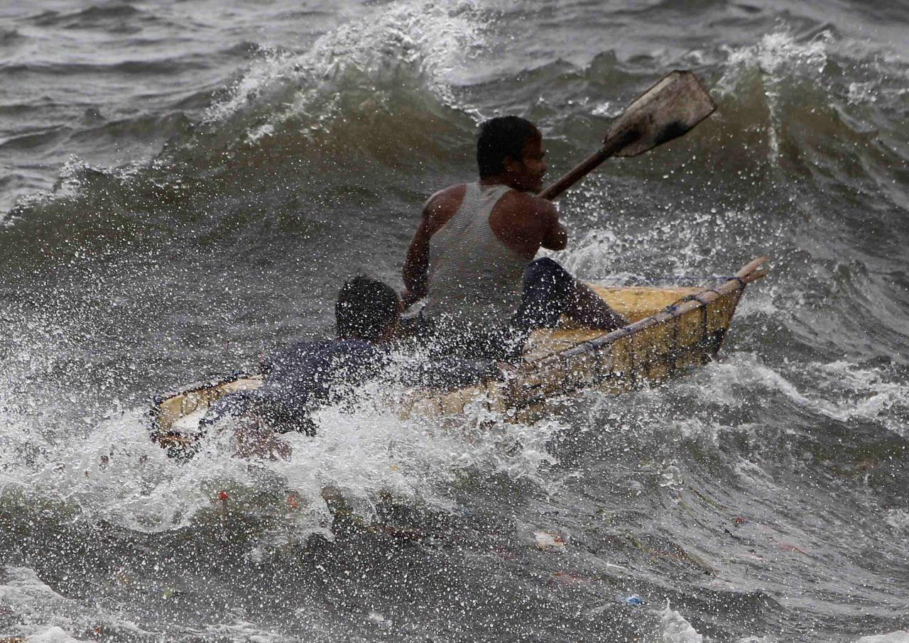 A man and a boy paddle through rough waves brought by Typhoon Usagi in Manila