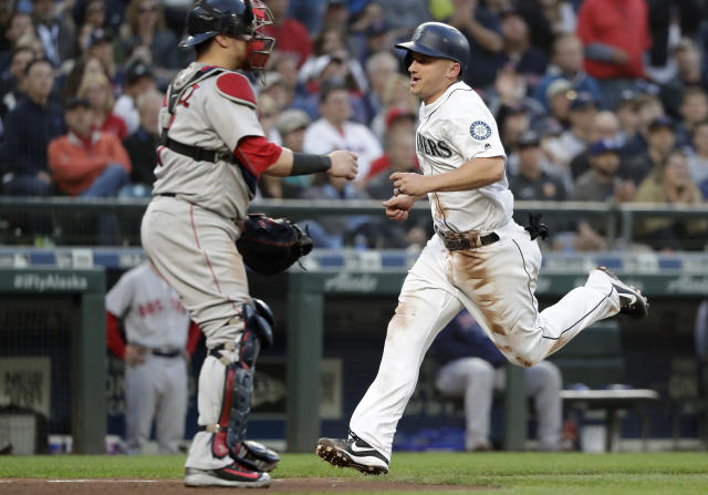 Seattle Mariners' Kyle Seager, right, scores as Boston Red Sox catcher Christian Vazquez waits for the ball during the fifth inning of a baseball game Thursday, June 14, 2018, in Seattle. (AP Photo/Elaine Thompson)
