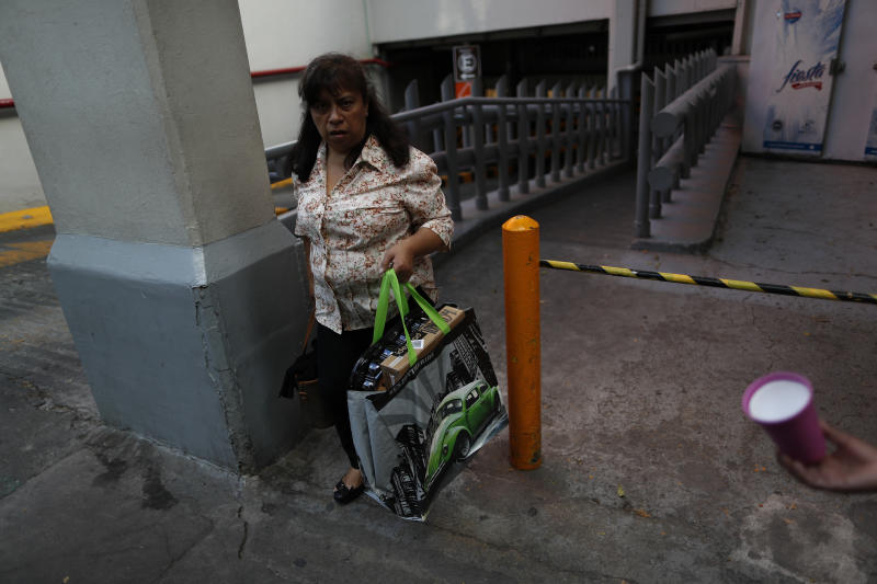 A woman carries a newly purchased reusable bag as she leaves a grocery store in Mexico City, Wednesday, Jan. 1, 2020. Stores stopped providing disposable plastic bags to their customers in compliance with a city law that took effect with the new year, and shoppers in Mexico's massive capital city could be seen Wednesday carrying handfuls of loose items, as well as purchases packed into reusable shopping bags or used plastic bags brought from home. (AP Photo/Rebecca Blackwell)