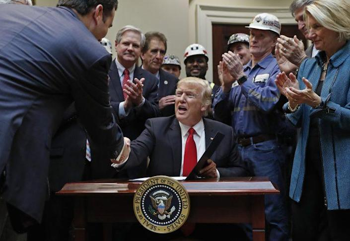President Trump is congratulated by coal miners and members of Congress after signing a bill nullifying the Stream Protection Rule, Feb. 16, 2017. (Photo: Carolyn Kaster/AP)