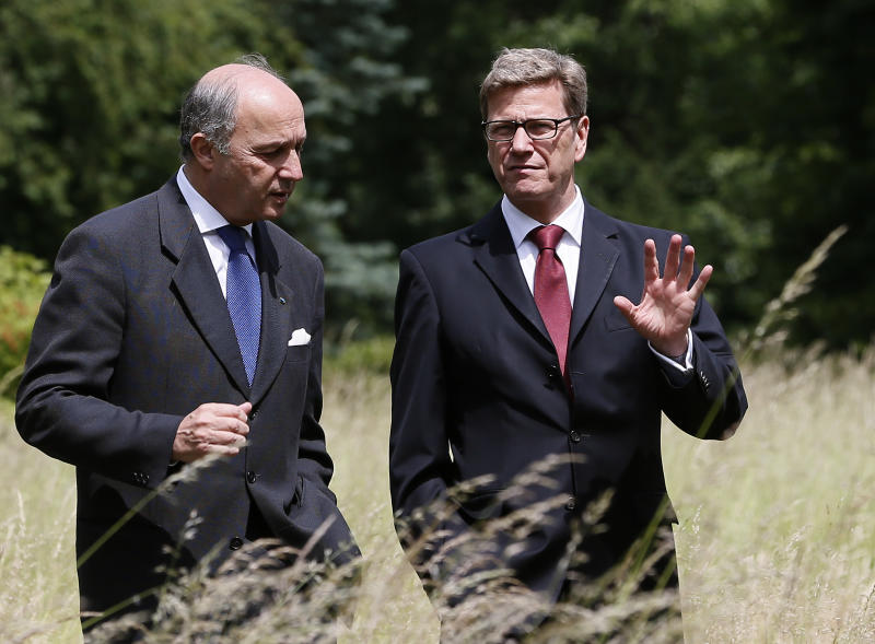 The Foreign Ministers of Germany Guido Westerwelle, right, and France, Laurent Fabius, left, walk in front of the guest house of the German Foreign Ministry Villa Borsig, in Berlin, Germany, Monday, June 4, 2012. (AP Photo/Michael Sohn)