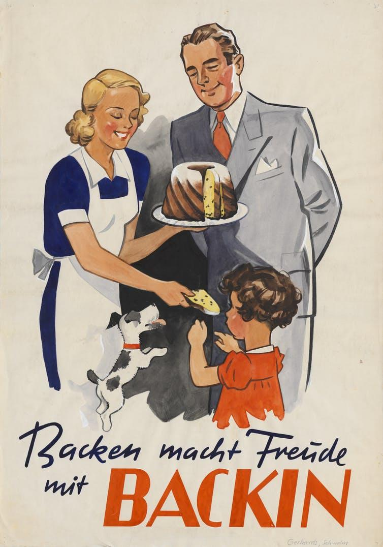 A woman in an apron stands next to a suited man. The woman gives some cake to a child, standing in front of them.