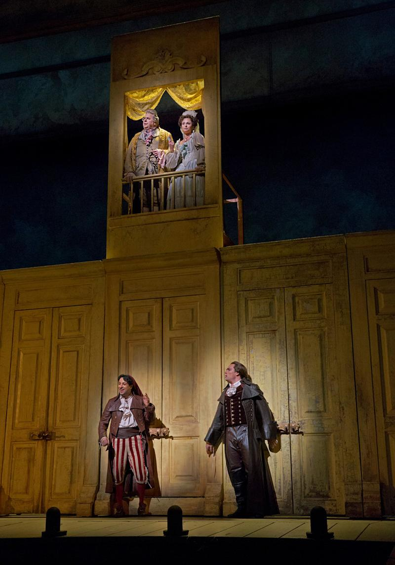"""In this Dec. 14, 2012 publicity photo, from left, Rodion Pogossov as Figaro and Alek Shrader as Count Almaviva, and balcony above, John Del Carlo as Dr. Bartolo and Isabel Leonard as Rosina are seen in Rossini's """"The Barber of Seville,"""" during rehearsal at the Metropolitan Opera in New York. (AP Photo/Metropolitan Opera, Ken Howard)"""